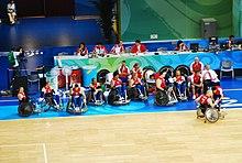 La photographie couleur montre l'équipe alignée entre le parquet de jeu et une longe table où semble siéger des personnalités officielles. Le photographe placé dans les tribunes a donné à son image une plongée qui permet de voir le groupe en entier. Le maillot est rouge et blanc, le bas est bleu.