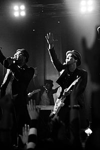 A black and white photograph of Bruno Mars performing with his band at a concert.