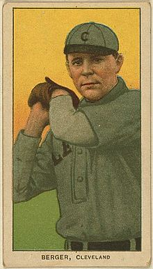 "A baseball card of a man wearing a gray baseball uniform with a black ""C"" on the cap holding his hands raised to the side of his head wearing a baseball glove on his left hand."