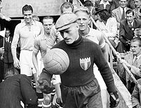 A man in dark football kit runs out onto the pitch before a football game, a hat on his head and a leather football in his right hand. The rest of the team follow behind.
