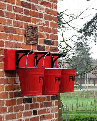 Fire bucket - Fire buckets hung on the wall of a railway station in Holt, England