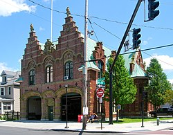 An ornate brick building with two large garages in front and two corresponding stepped point sections on the roof behind a traffic signal at the intersection of Delaware Avenue and Marshall Street, seen from the far corner.