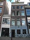 foto van Huis met gevel onder rechte lijst, met zandstenen onderpui en deur met beglaasde panelen en snijraamhekken