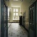 Interieur, overzicht van een gang met een lambrisering van geglazuurde tegels en tegelvloer met uitzicht op een raam - 's-Gravenhage - 20387480 - RCE.jpg
