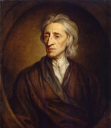 Three-quarter length portrait of a man with a shock of neck-length white hair wearing a loose brown robe and white shirt.