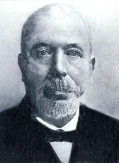 Black and white photograph of elder and bald John Houlding, wearing beard and bow tie.