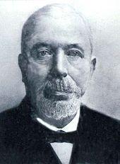 Fotografía en blanco y negro del anciano y calvo John Houlding, con barba y pajarita.