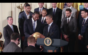 Kawhi Leonard presents ball to President Obama 2 2015-01-12.png