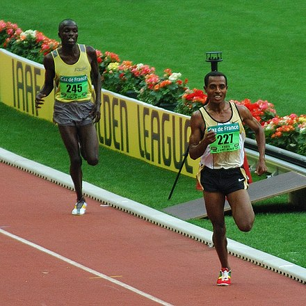 Kenenisa Bekele leading in a long distance track event - Track and field