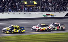 Matt Kenseth (in the blue and yellow car with the 17 number) is leading Greg Biffle in the Black, White and Red car displaying the number 16. Biffle is closely followed by Dale Earnhardt Jr. driving a car with the number 88 with a silver color scheme.