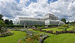 A large greenhouse with rounded ends and sides sits in the middle of groomed grass and flower beds.