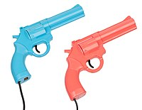 Three colored plastic lightgun game controllers resembling real-world guns, laid out on a floorspace