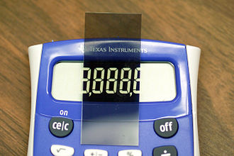 Liquid-crystal display - LCD in a Texas Instruments calculator with top polarizer removed from device and placed on top, such that the top and bottom polarizers are perpendicular. Note that colors are inverted.
