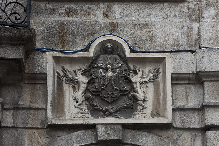 English:  Low relief, to the coast of arm of the city, on the right of the balcony of honor.