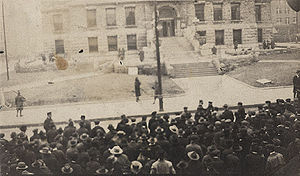 A discolored photo of a mob gathered outside a courthouse