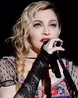 Madonna in a black dress in front of a microphone, holding it with her right hand