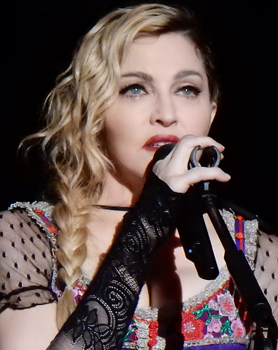 A closeup photo of Madonna with shoulder-length wavy blonde hair, wearing a colorful, low-cut blouse, holding a microphone to her mouth with her right hand.