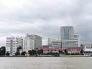 """A large complex of buildings, most over ten storeys high, on the bank of a river; one bears a sign with the words """"SIRIRAJ HOSPITAL""""; another says """"FACULTY OF NURSING"""""""