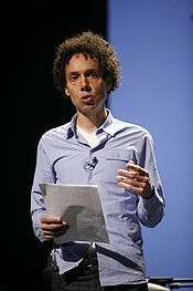 A man holds a piece of paper while he gives a speech.