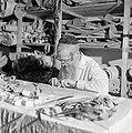 Man maakt thorarollen achter een volle werktafel, Bestanddeelnr 255-2340.jpg