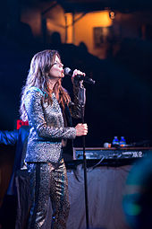 A woman with long brown hair wearing a silver jacket and pants, singing into a microphone