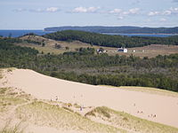 People on sandy dunes overlooking farmland and the lake