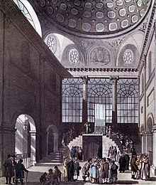 People gather in groups in a very high hall with arches, high windows, and staircases.