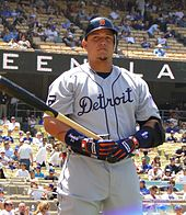 "A man in a grey baseball uniform with the word ""Detroit"" written across the chest holding a baseball bat."