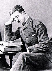 Druitt, a thin young man with dark hair parted in the middle and a small moustache, sits at a table and reads a book