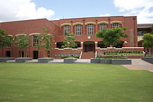 A large red brick building surrounded by trees.