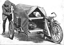 A man securing the canvas cover on a motorcycle sidecar containing two patients