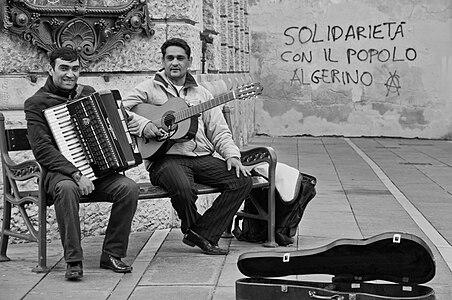 Una coppia di musicisti di strada stranieri si diverte, alle spalle un'attualissima scritta su un muro, magari dedicata alla propria patria...ma scritta da altri... Musica e solidarietà?