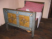 A bed with a chamber pot under it.