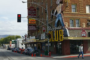 """brick casino with hints of art deco style. A faded sign on the corner is a prospector with a pick axe with the words """"Nevada Club"""" next to a vintage mechanical slot machine."""