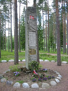 A stone monument in a forest clearing, adorned with a plaque and small Norwegian flag