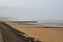Plaża zakończona wałem przeciwpowodziowym, z widocznym w oddali gaikiem