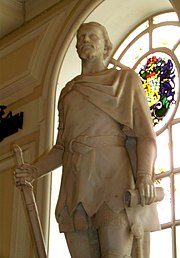 The statue of a man in a tunic and short cape clasped at his right shoulder, sculpted in white stone. The figure, set indoors with its back to an arched window, holds a down-pointed sword in his right hand and a scroll in his left.