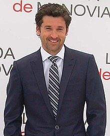 Patrick Dempsey smiling, wearing a navy blue suit.