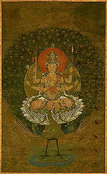 Frontal view of a deity with six arms seated on a peacock.