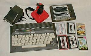 Commodore Plus/4 - Commodore Plus/4 with accessories. Clockwise from top left: power supply, joystick, 1531 tape recorder with tapes.