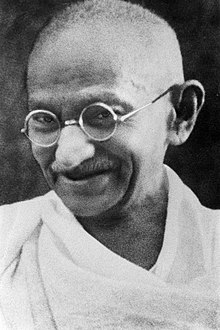 The face of Gandhi in old age – smiling, wearing glasses, and with a white sash over his right shoulder
