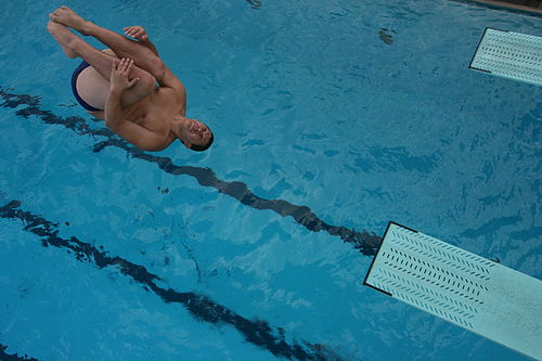 A male diver performs a reverse in the tuck position from a 3-meter springboard