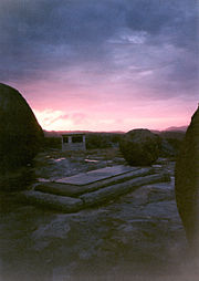 Daybreak over a rough, rocky landscape, with trees visible near the horizon. In the foreground a plain, rectangular grave is visible. Behind it, at a distance of perhaps 20yards, a white, oblong, flat-topped structure can be seen.