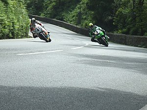 Sarah's Cottage, Isle of Man - View from Sarah's Cottage towards the Glen Helen area, with Ian Hutchinson cornering inside Ian Lougher in Senior TT during 2010, demonstrating that some places on the course have more variation in racing lines than others
