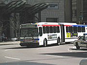 A white bus in two sections, connected by a black expansion joint, goes into a turn.