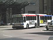 Un bus blanco en dos secciones, conectado por una junta de expansión negra, entra en una curva.
