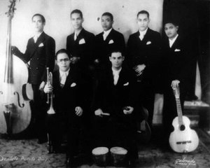 "Tres (instrument) - The Septeto Puerto Rico in the early 1930s. Guillermo ""Piliche"" Ayala is standing on the right with the first known Puerto Rican tres."