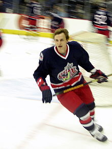 A hockey player in a blue, red and white uniform looks into the distance as he makes a turn while skating.
