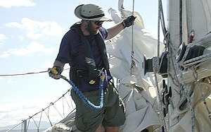 Single-handed sailing - A sailor tethered to the boat for safety as he reefs sails.