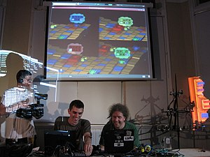 "Slub (band) - Dave and Alex of Slub performing live in London. The left screen shows one performer's CLI, the right shows the other performer's ""Scheme bricks"" coding interface, and the top shows a custom-made game environment through which audience members influence the music generation."